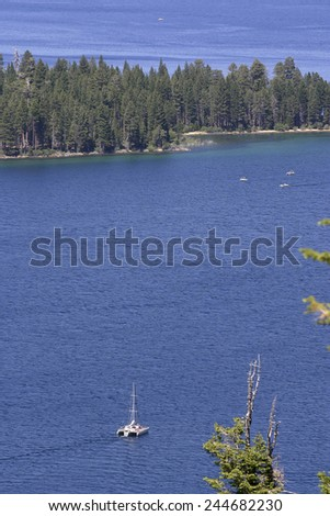 An aerial view of Lake Tahoe in California with pine forests, blue water and boats - stock photo