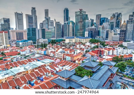 An aerial view of Singapore's Chinatown with its distinct low-rise, Baroque-Victorian style shophouses against the backdrop of the city's financial district and skyscrapers in the background.