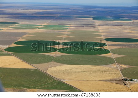 An aerial view of the crop circles created in farm fields by center pivot sprinklers. - stock photo