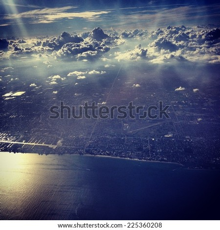 An aerial view of the ocean, land, and puffy clouds in the sky. - stock photo