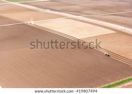 An aerial view of tractors planting potatoes in the fertile farm fields of Idaho. - stock photo