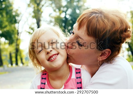 An affectionate mom kissing her little daughter. Happy daughter laughing. - stock photo