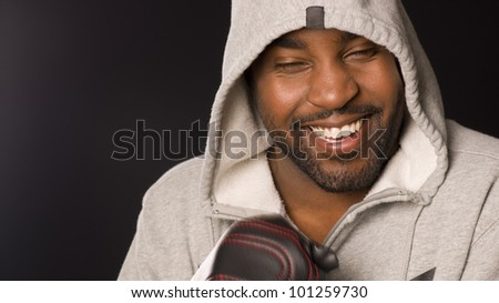 An African American boxer laughs eyes closed wearing work out gloves - stock photo