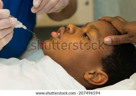 An African American boy gets an injection of local anesthesia into a wound. - stock photo