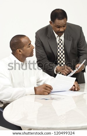 An African American business people discussing over financial bills in the office - stock photo