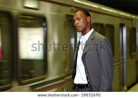 An African-American businessman awaits his commuter train - stock photo