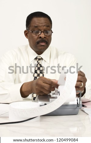 An African American businessman with expense receipt and calculating machine at office - stock photo