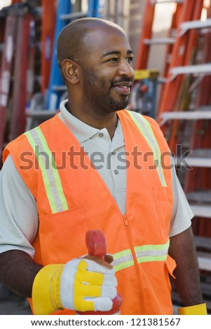 An African American construction worker wearing protective work wear with ladders in the background