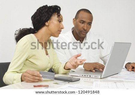 An African American couple paying bills online at home