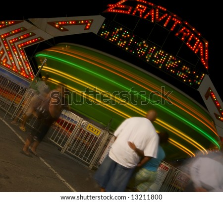 An African American couple stand in line and wait for their turn on a spinning carnival ride at night