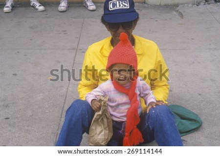 An African-American father and son sitting on a curb in New Orleans - stock photo