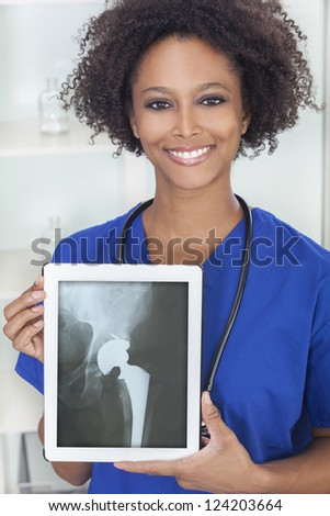 An African American female woman medical doctor in hospital holding a tablet computer with a hip replacement patient X-ray on the screen - stock photo