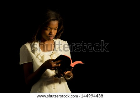 An African American girl reads her Bible. - stock photo
