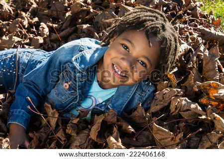 An African American girl smiling in a pile of leaves. - stock photo