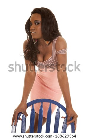 An African American holding on to her blue chair looking. - stock photo