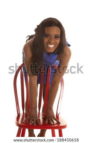 An African American leaning over a red chair with a smile on her face.