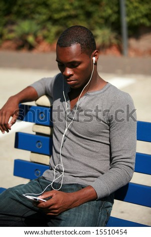 an african american male model listens to music on his personal mp3 music player - stock photo