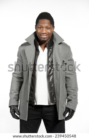 An African American male model wearing a gray jacket and white t-shirt underneath with black pants and black leather gloves in a studio setting. - stock photo