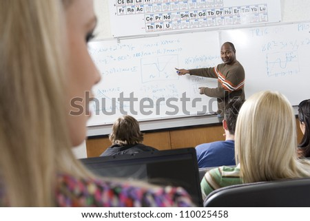 An African American male teacher teaching students - stock photo