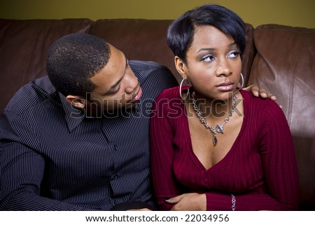 An african american man attempts to cheer up his sad girlfriend on the couch - stock photo