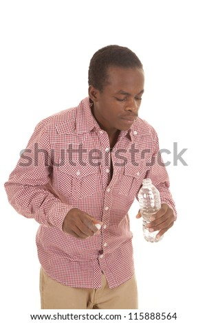 An African-American man holding on to his water bottle and lid and looking into the bottle - stock photo