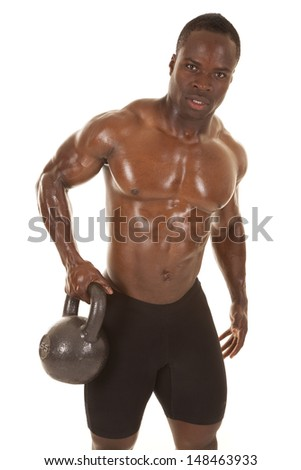An African American man shirtless holding a weight.