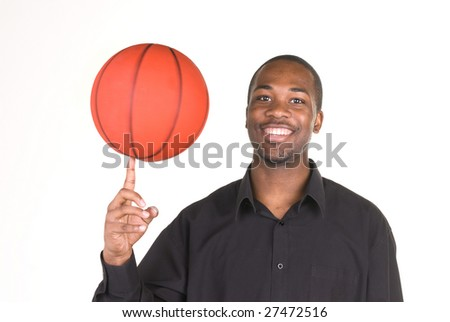 An African American man spins a basketball on his finger. - stock photo