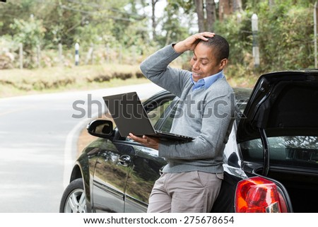 an African American man standing beside the car on the road with hand on his head looking at the screen of your laptop - stock photo