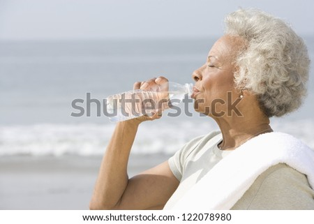An African American senior woman drinking water from bottle with sea in the background - stock photo