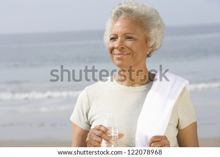 An African American senior woman holding bottle of water at beach