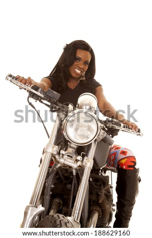 An African American sitting on a motorcycle in her boots and leggings.  She has a smile on her face. - stock photo