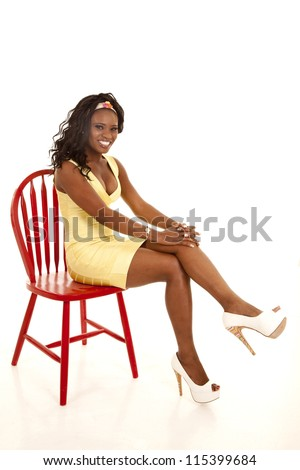 An African American sitting on a red chair in her yellow dress with a smile on her face. - stock photo