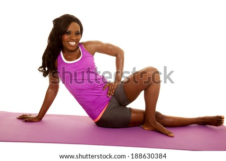 An African American sitting on her fitness mat stretching. - stock photo