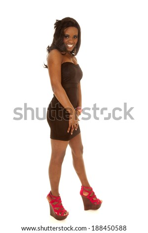 An African American standing in her black dress and red shoes with a smile on her face.
