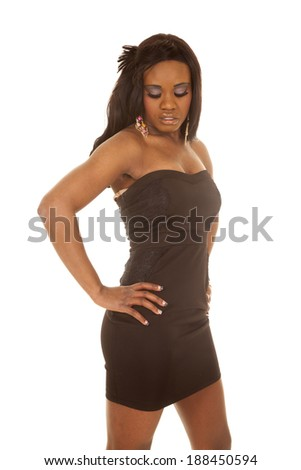 an African American standing in her dress looking down. - stock photo
