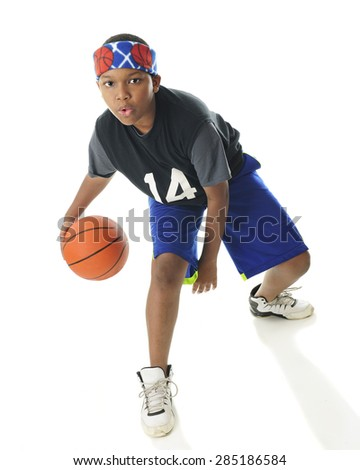 An African American tween basketball player actively dribbling his ball.  On a white background. - stock photo