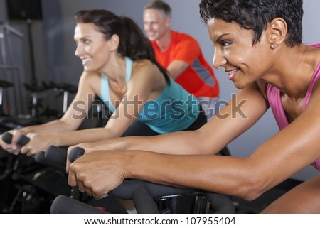 An African American woman and middle aged friends on exercise bikes at a gym - stock photo