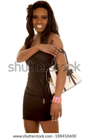 An African American woman in her black dress with a purse on her shoulder.