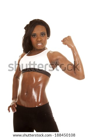 an African American woman in her fitness clothing flexing her arm.