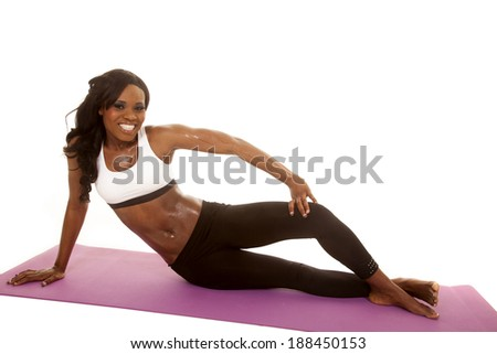An African American woman in her fitness clothing sitting on her fitness mat.