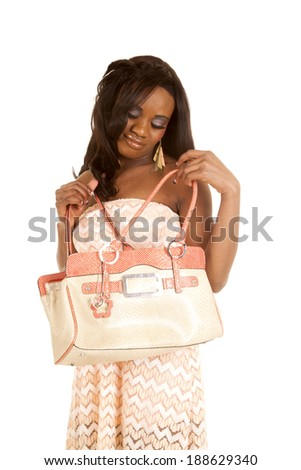 An African American woman in her peach dress looking down into her bag.