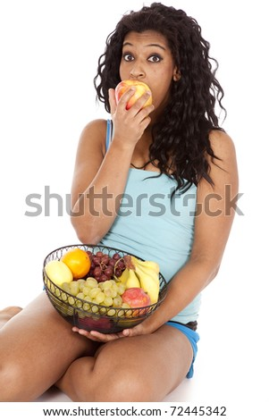 An African American woman is biting an apple. - stock photo