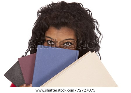 An African American woman is peaking out from behind a stack of books. - stock photo