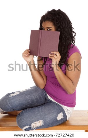 An African American woman is peaking over a book. - stock photo