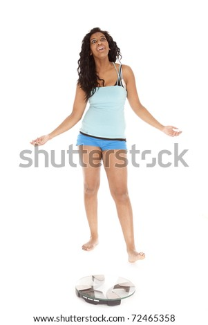 An African American woman is standing by the scales. - stock photo
