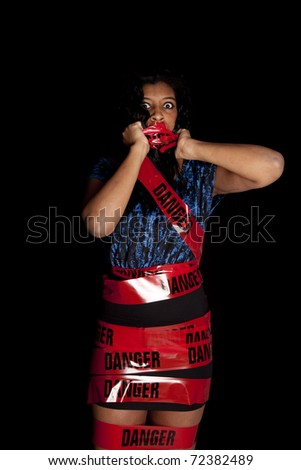 An African American woman is standing scared wrapped in danger tape. - stock photo