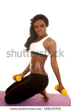 an African American woman kneeling down and holding on to her weights.