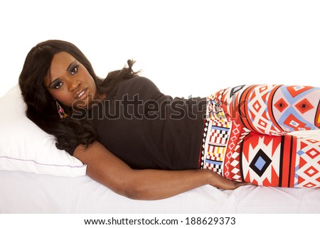 An African American woman laying on her side, in her leggings with designs.