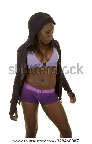 An African American woman posing her body in her fitness clothing.
