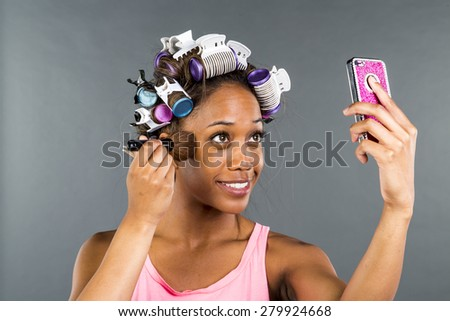 An African American woman putting on makeup - stock photo